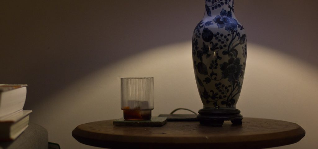 Glass of English Red Vermouth alongside a table lamp