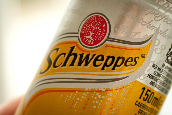 A closeup of a mini can of Schweppes Tonic
