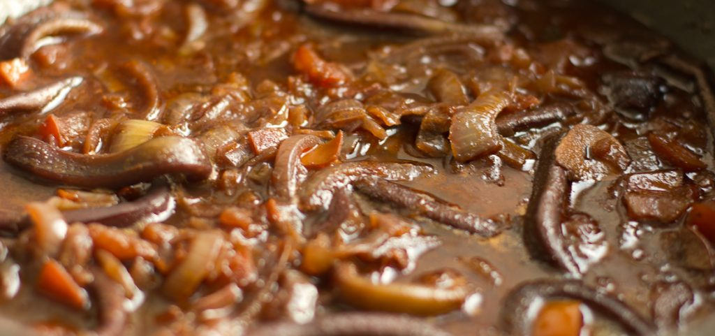 Squid simmering in a dark red wine sauce