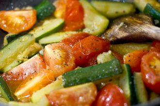 Courgette fingers and tomato quarters frying in oil